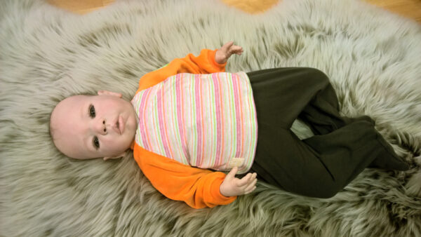 Babyshirt-Wickelshirt-Sreifen-rosa-Strick-Aermel-beide-orange-Nicky-von-oben-mit-Puppe