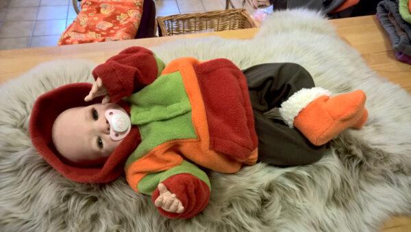 Fleecepulli-Fliegenpilz-rot-orange-grün-von-vorn-mit-Puppe