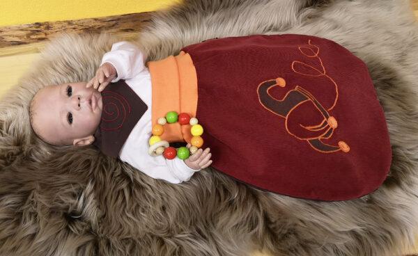 Strampelsack-Narr-rot-braun-mit-Puppe